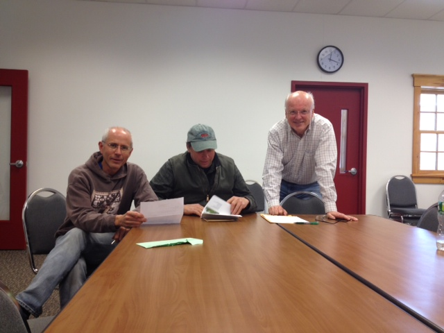 Doug Mayer, John Scarinza and Mark Kelley open the bids for the trailhead project.