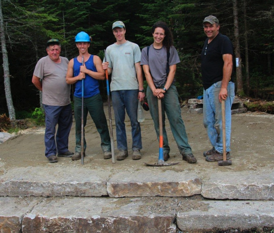 Five proud workers posed for a photo after the new trail and canoe access were nearly completed on Thursday, July 30, two days before the Aug. 1 Forest tour: Auvie Kenison of Randolph, who operated a mini-excavator; three Randolph Mountain Club trail crew members — project leader and third-year member Sarah Allen of Nashville, Tenn., 1st year crew member and former caretaker Justin Taylor, and 3rd year trail crew member Brian Behr of Tamworth — and John Scarinza, chairman of the Randolph Forest Commission. (Photo by Edith Tucker.)