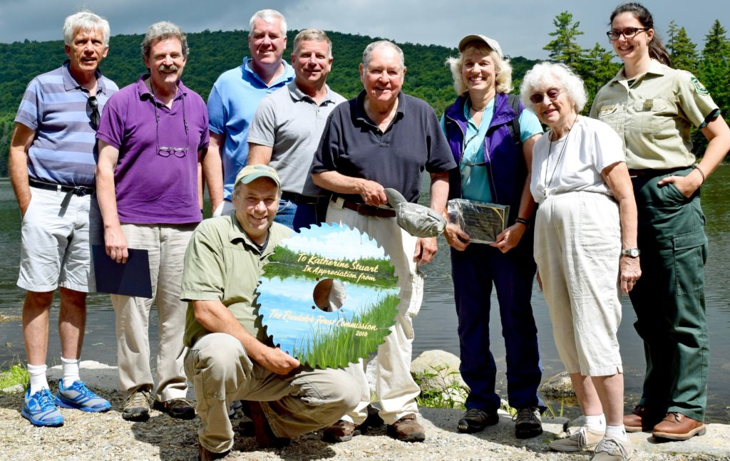 Now-retired Androscoggin District Ranger Katie Stuart of Shelburne, 3rd from right, holds the plaque honoring her collaboration with the Randolph Community Forest presented to her on Aug. 6 by Randolph town moderator David Willcox, 4th from right, at the Pond of Safety. Also honoring her: Forest commissioner Walter Graff, left, Chuck Henderson representing U.S. Sen. Jeanne Shaheen, state Sen. Jeff Woodburn, WMNF Supervisor Tom Wagner, Rep. Paula Bradley, prime sponsor of legislation creating the Commission & Forest, and today's Androscoggin District Ranger Jennifer Barnhart. Randolph Forest Commission chairman John Scarinza, front row, holds the saw blade he presented to Stuart. (Edith Tucker photo)